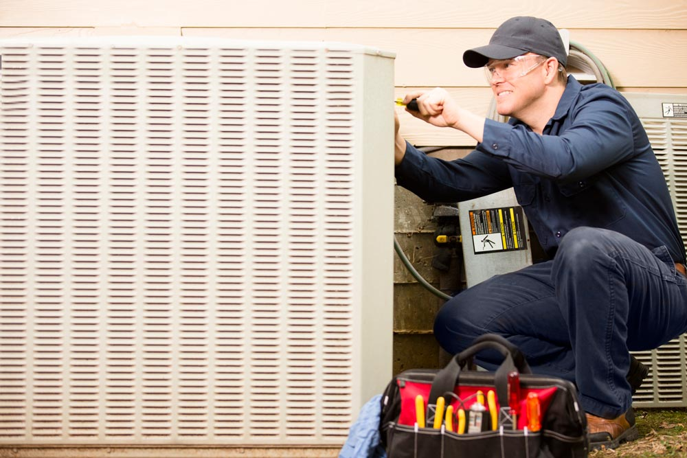 Cam Heating and Cooling repairman working on air conditioning unit outside house